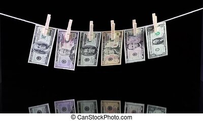 Dirty US dollar banknotes hanging from a clothesline and...