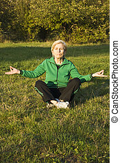 Older woman yoga in park
