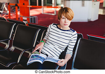 woman reading newspaper at Charles de Gaulle airport, Paris.