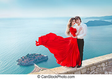 Romantic young couple in love over blue sea shore background...