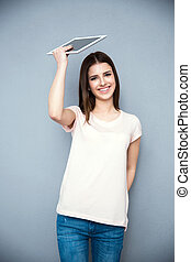 Young happy woman holding tablet computer over gray background