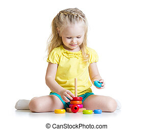child playing with color pyramid toy - cute kid girl playing...