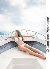 Young brunette woman tanning on the bow of a boat