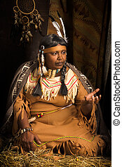 Ethnic stories - Weathered mature tribal female storyteller...