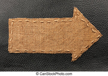 Arrow of burlap, lies on a background of leather, with place...