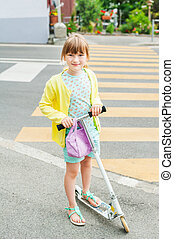 Pretty little girl is going to cross the road alone