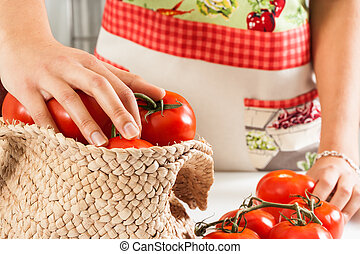 Picking tomatoes - Woman with an apron picking tomatoes