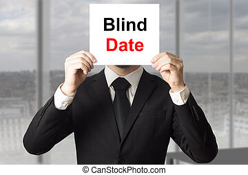 businessman hiding face behind sign blind date - businessman...