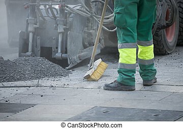 Worker operating asphalt paver machine during road...