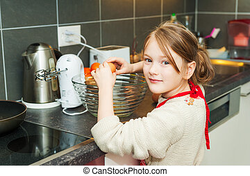 Adorable little girl of 7 years old helping in the kitchen