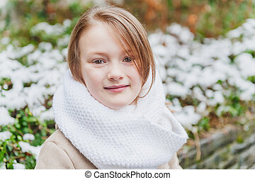 Close up winter portrait of a cute little girl wearing big and warm wool knitted scarf