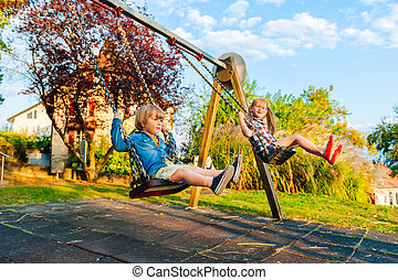 Adorable kids having fun outdoors on sunset, playing on a...