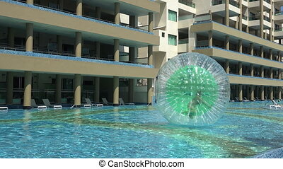 Pool Human Hamster Ball Playing - A medium pan of the pool...