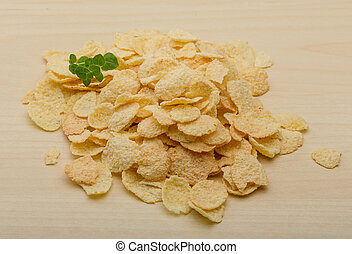 Cornflakes heap on the wood background