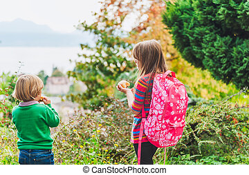 Two adorable kids having a snack outdoors after school,...
