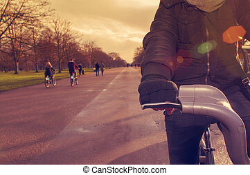 man riding a bicycle in Hyde Park in London, United Kingdom...