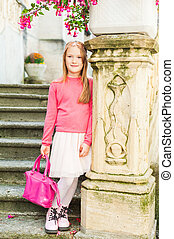 Outdoor portrait of a cute little girl, wearing pink...