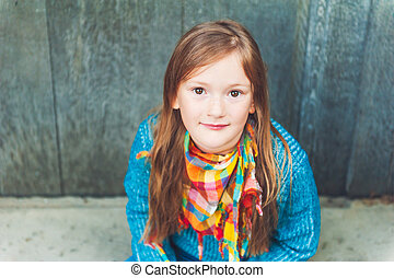 Outdoor portrait of a cute little girl wearing colorful scarf