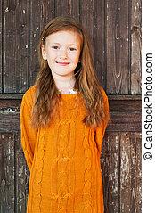 Outdoor portrait of a cute little girl standing next wooden...
