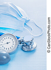 masks and stethoscope with blood pressure monitor on blue backgr