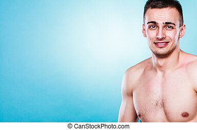 Sporty and healthy muscular man portrait blue background