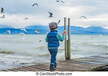 Adorable toddler boy feeding birds on a cold weather, back...