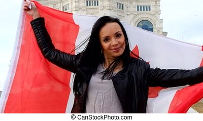 Happy brunette girl with Canadian flag outdoors - Happy...