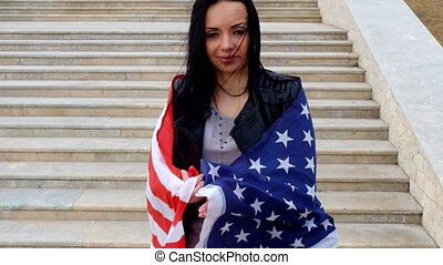 Happy latino women posing with stars and stripes flag...