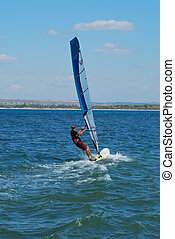 Windsurfer - Young man windsurfing close from a coastal line...