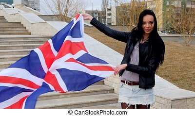 Smiling latina brunette holding Union Jack flag waving by...
