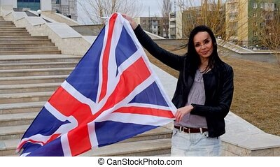 British latino woman holding Union Jack flag waving in the...