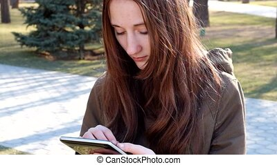 Redhead teen girl using tablet PC outdoors full HD footage.