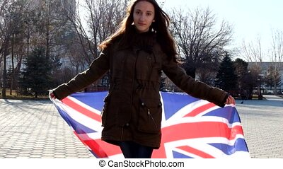 Teen girl with Union Jack waving by the wind and smiling...