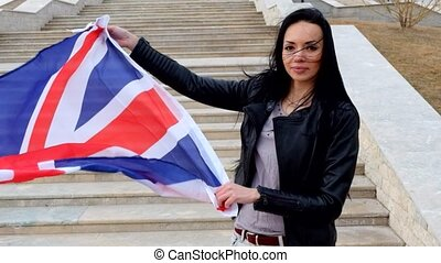 Brunette women with UK Union Jack flag posing smiling...