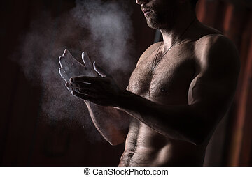 hands with chalk - cropped view of a male gymnast dusting...