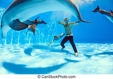 on the bottom of dolphinarium - two men and three dolphin...