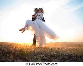 Husband carries his beloved wife in arms - Husband carries...