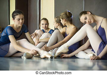 Five young dancers in the same dance costumes, resting...