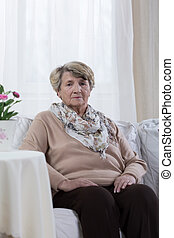Sad elder woman being alone at home