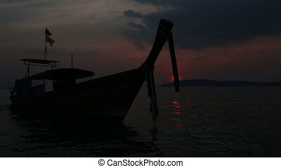 longtail boat rolls on waves at sunset - silhouette of...