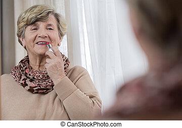Senior lady applying lipstick - Portrait of senior lady...