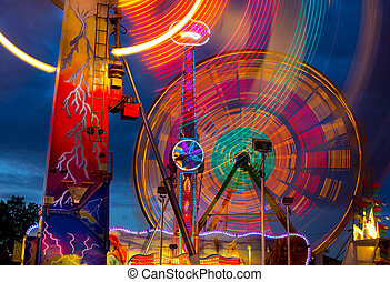 Ferris Wheel at Night - Colorful nighttime view of rides at...
