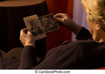 Grandma looking at grandchilds photos - Grandma sitting in...