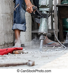 Builder worker with pneumatic hammer drill equipment at...