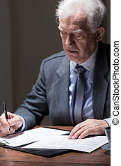 Aged businessman doing paperwork - Aged businessman sitting...