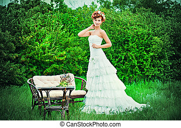fiancee - Lovely elegant red-haired bride stands on the lawn...