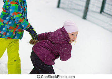 Children throwing snowballs in snowy winter park