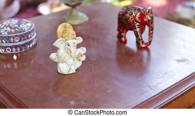 small statues of indian idols stand on table at indian...