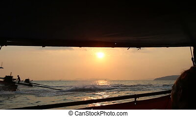 longtail boat floats at sunset - silhouette of thailand...