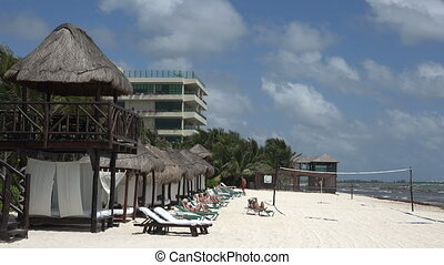 Palapa Sunning on Beach - Mexico beach palapas lined up and...